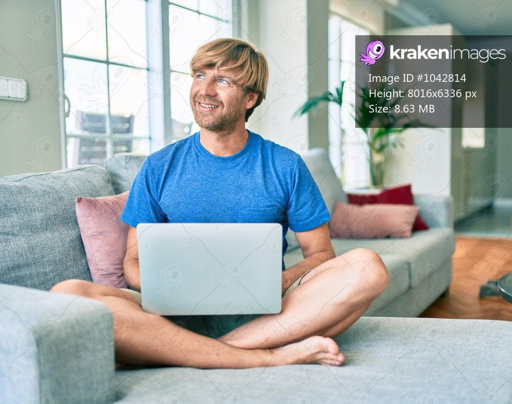 Middle age handsome caucasian man relaxing at home working with computer laptop on the sofa