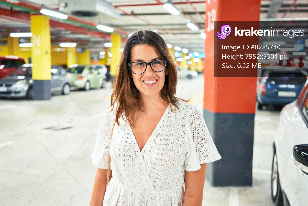 Young woman smiling confident at underground parking lot around cars and lights