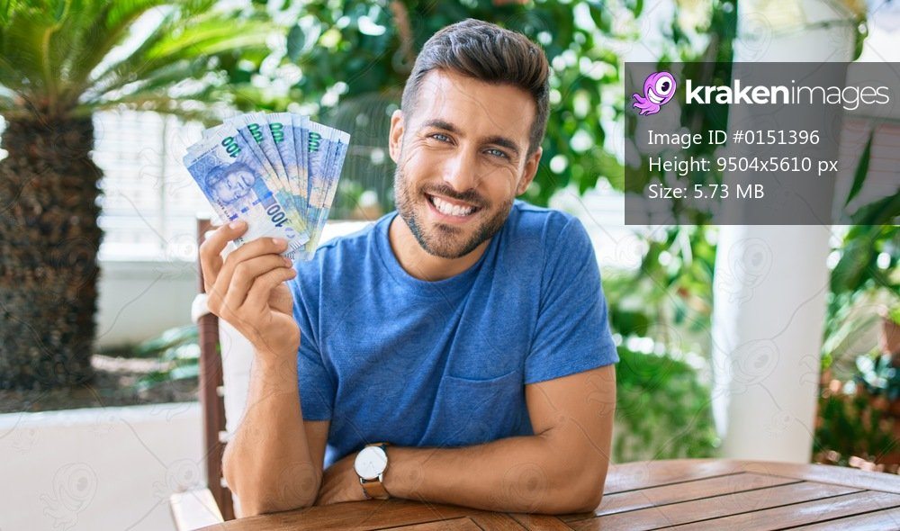 Young hispanic man smiling happy holding south african rands banknotes at the terrace.