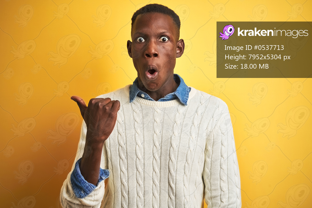 African american man wearing denim shirt and white sweater over isolated yellow background Surprised pointing with hand finger to the side, open mouth amazed expression.