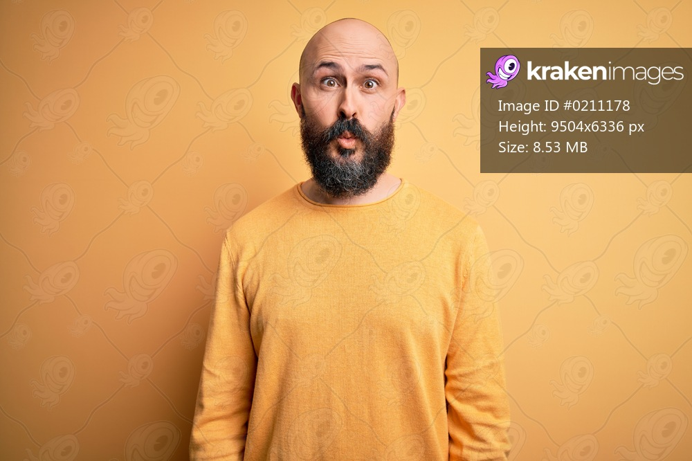 Handsome bald man with beard wearing casual sweater standing over yellow background making fish face with lips, crazy and comical gesture. Funny expression.