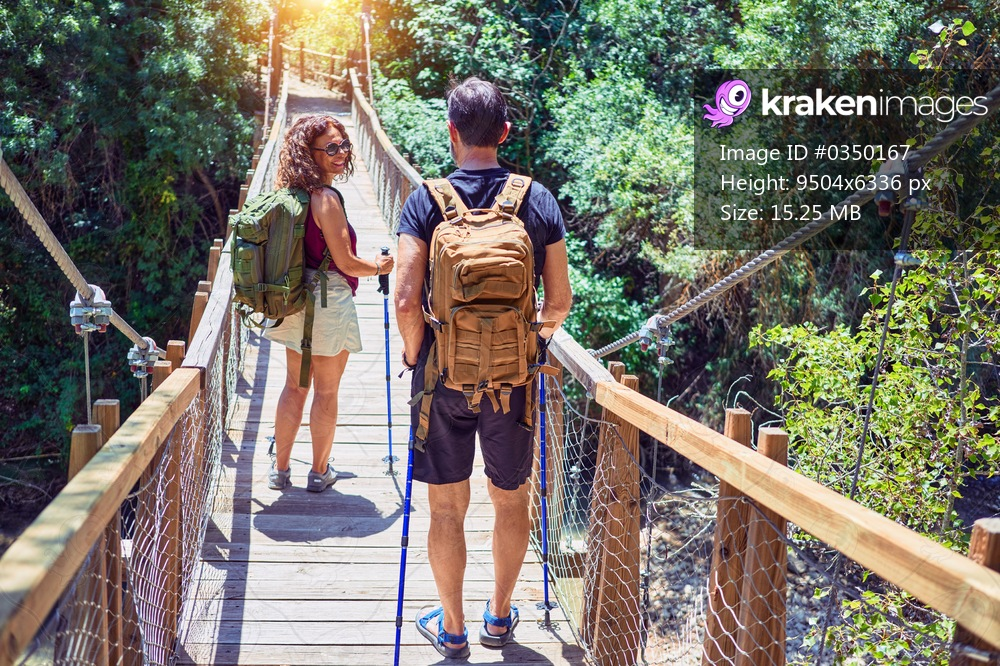 Beautiful couple of hiker wearing explorer clothes and  backpack. Walking on back view at runway over forest landscape background.