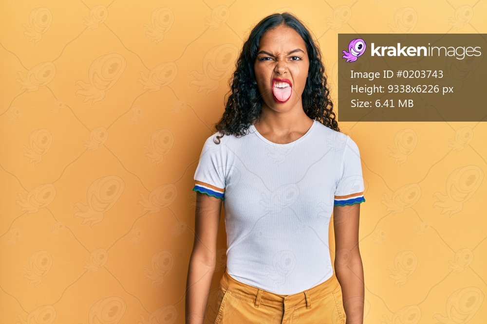 Young african american girl wearing casual clothes sticking tongue out happy with funny expression. emotion concept.
