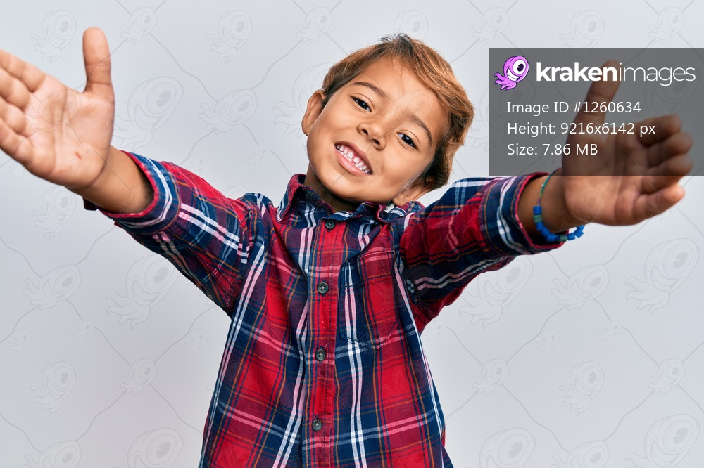 Adorable latin kid wearing casual clothes looking at the camera smiling with open arms for hug. cheerful expression embracing happiness.