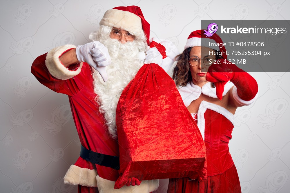 Senior couple wearing Santa Claus costume holding sack over isolated white background with angry face, negative sign showing dislike with thumbs down, rejection concept