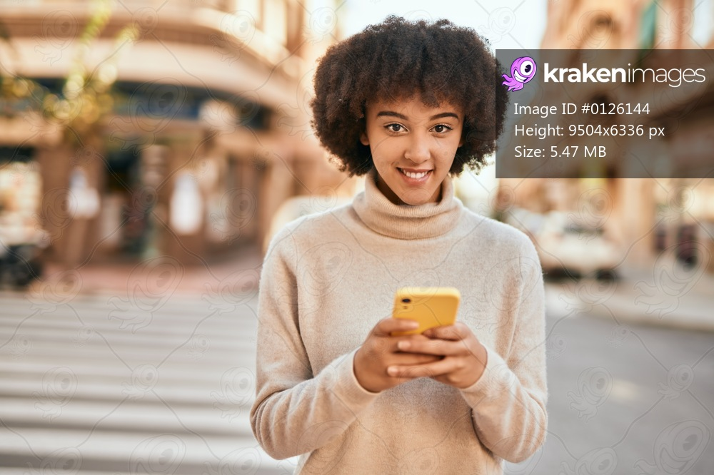 Young hispanic girl smiling happy using smartphone at the city.
