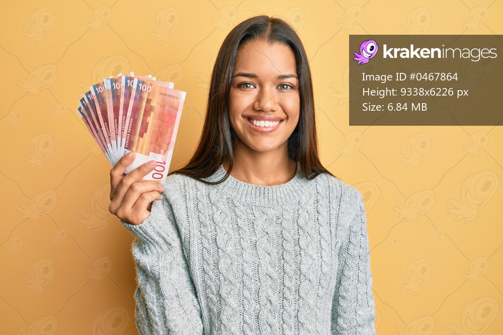 Beautiful hispanic woman holding 100 norwegian krone banknotes looking positive and happy standing and smiling with a confident smile showing teeth