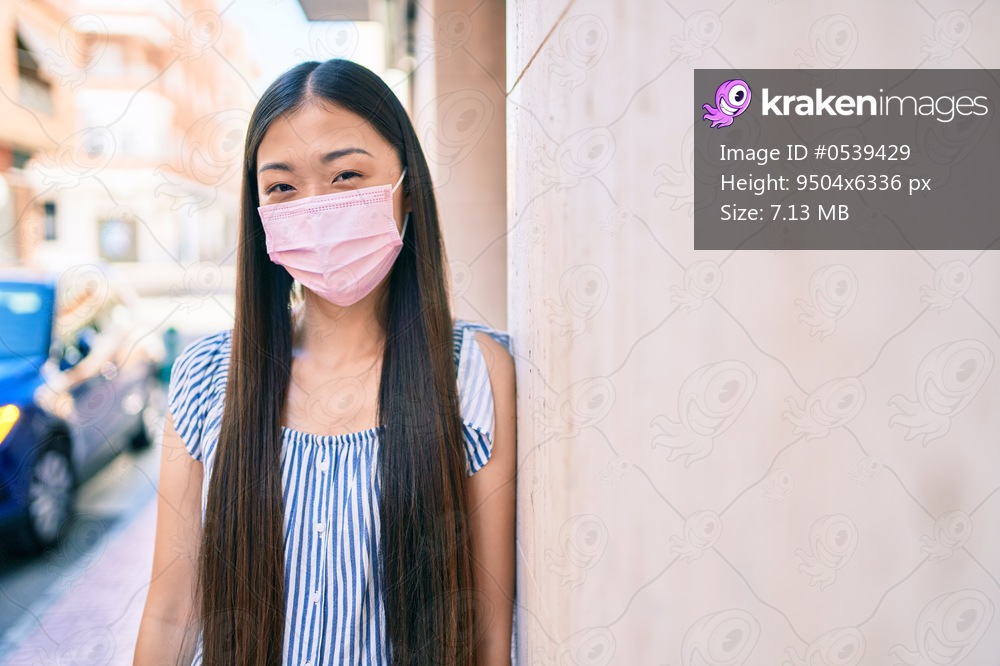 Young chinese woman wearing medical mask leaning on the wall at street of city.
