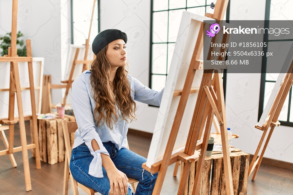 Young hispanic artist woman painting on canvas at art studio looking to side, relax profile pose with natural face and confident smile.