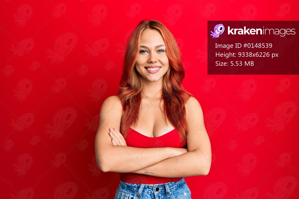 Young beautiful redhead woman wearing casual clothes over red background happy face smiling with crossed arms looking at the camera. positive person.