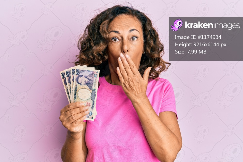 Middle age hispanic woman holding japanese yen banknotes covering mouth with hand, shocked and afraid for mistake. surprised expression