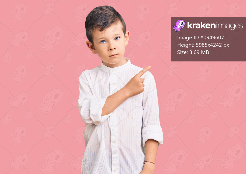 Cute blond kid wearing elegant shirt pointing with hand finger to the side showing advertisement, serious and calm face