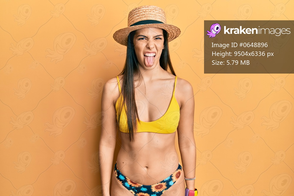 Young hispanic woman wearing bikini and summer hat sticking tongue out happy with funny expression. emotion concept.