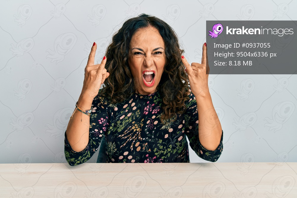 Beautiful middle age woman wearing casual clothes sitting on the table shouting with crazy expression doing rock symbol with hands up. music star. heavy concept.