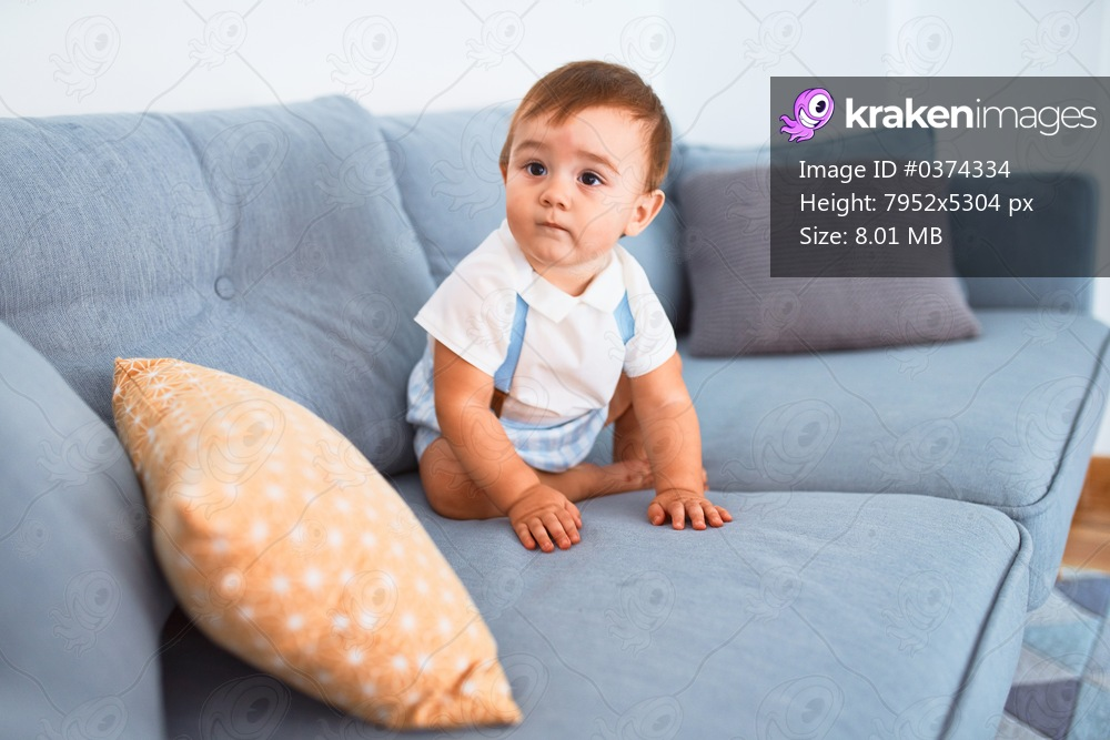 Adorable toddler sitting on the sofa at home